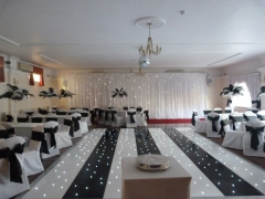 Linen covers with black taffeta and feather centrepieces
