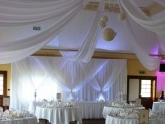 Grecian-backdrop-white-uplighters-and-non-swag-front-table